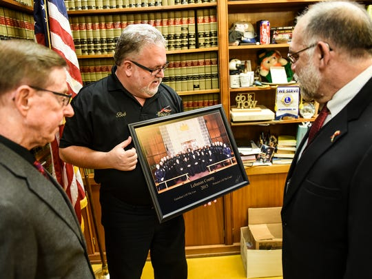 Sheriff Bruce Klingler, (left) Robert Howard (center) and President Judge John Tylwalk (right) look at the photo after Howard made of all five Lebanon County judges and all 21 sheriff deputies on Friday, March 4, 2016. This is the first time a picture like this has been taken. The photo was taken on Oct. 19, 2015 and Howard donated his services and the print which hangs in the judge's chambers.