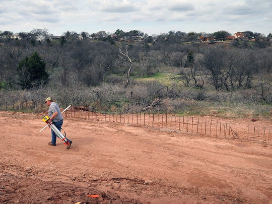 A surveyor moves his equipment after taking measurements for one of the many retaining walls along the Circle Trail in the Wichita Bluff Nature Area. The section of trail is just over one mile and includes walls, bridges, pavilions, lighting, two entryways and several scenic overlooks.