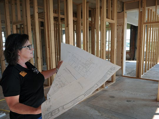 Judy Kurani, property manager for Metrolife Properties, looks at floor plans in one of the 28 apartment units being constructed at City Center Apartments in downtown and Eighth Street and Indiana Avenue