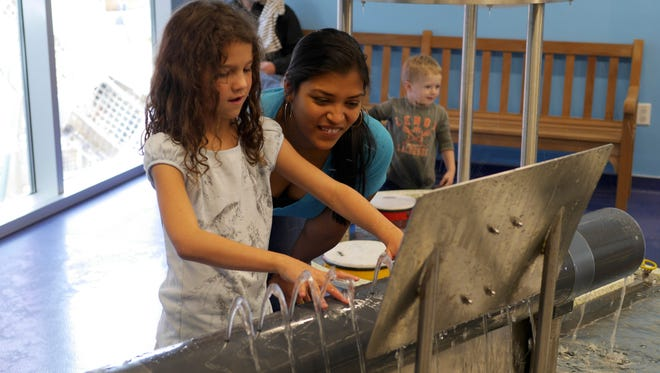 At Currents, children learn about fluid dynamics by playing with water. A visitor covers the holes on the hydraulophone, a large water pipe, to make music.