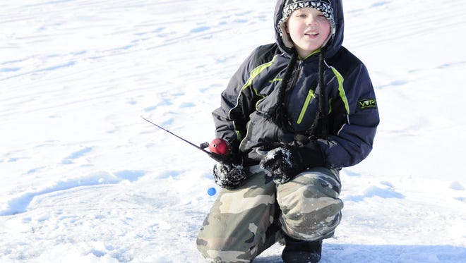 Logan Williams ice fishes Dec. 30, 2017, at the Lexington Harbor. The state is warning people that late-season ice might not be safe for winter activities.