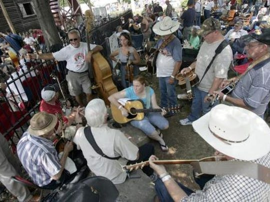 A group of musicians play together in the shade at a past Uncle Dave Macon Days.