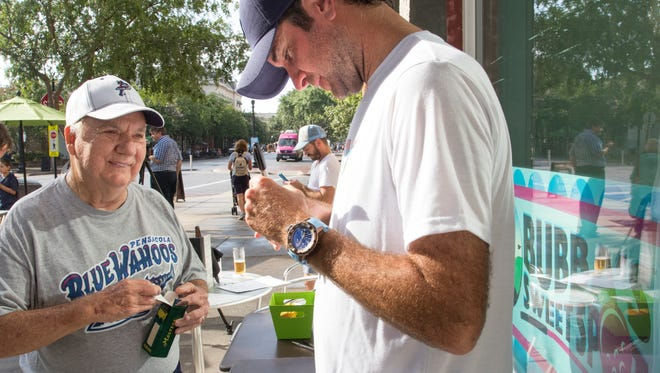 Henry Willett watches as professional golfer Bubba Watson signs a golf ball for him during the grand opening of Bubba's Sweet Spot in downtown Pensacola, FL on Friday, July 22, 2016.