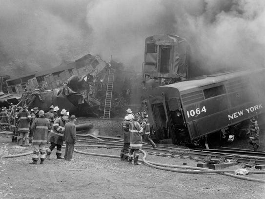 Firemen look at the tangled wreckage of two trains