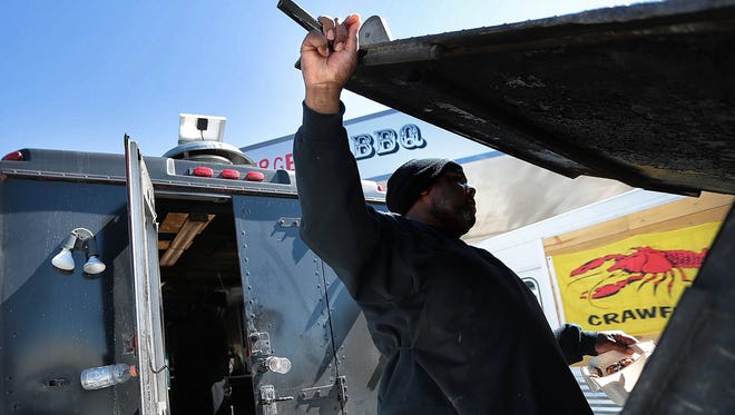 Damion Lovett pulls chicken off the grill at the Royal Flavors Xpress food truck during lunch time at the new Memphis Food Truck Park, located at at the corner of Winchester and Old Getwell.