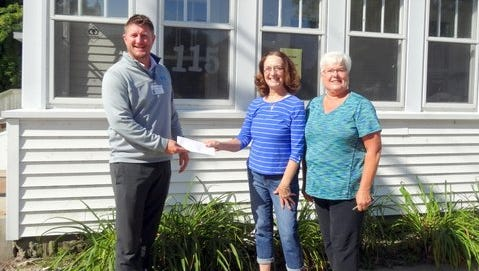 Andy Starr, left, president of the board of directors for the 115 Club, accepts the donation from Linda Kintopf and Bev Luethge of St. Peter's Outreach Team.