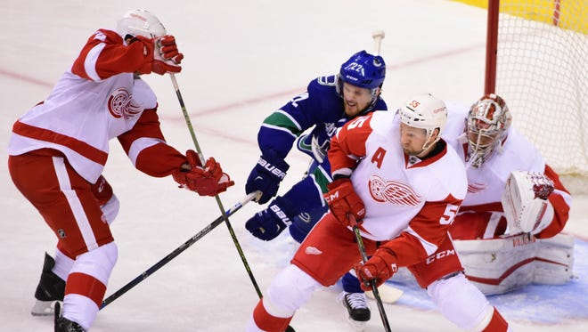Canucks forward Daniel Sedin (22) reaches for the puck against Red Wings defenseman Niklas Kronwall (55) during the second period at Rogers Arena Saturday.