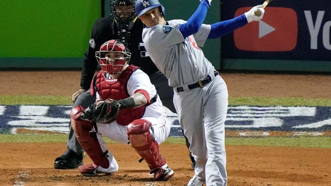 FILE - In this Oct. 24, 2018, file photo, Los Angeles Dodgers' Manny Machado, right, hits a single in front of Boston Red Sox catcher Christian Vazquez during the fourth inning in Game 2 of the World Series baseball game in Boston. Machado, Bryce Harper, Craig Kimbrel and Dallas Keuchel will not be around when the bat and ball bags are opened at spring training throughout Florida and Arizona this week. They are among the dozens of free agents still looking for jobs. (AP Photo/Elise Amendola, File)
