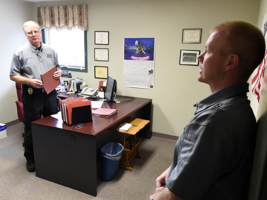 Baxter County parole officers Harry Nuccio, left, and Bobby Hicks talk about several home visits they planned on making Wednesday. Nuccio says parole officers are aware of how their work can impact populations in county jails and state prisons.