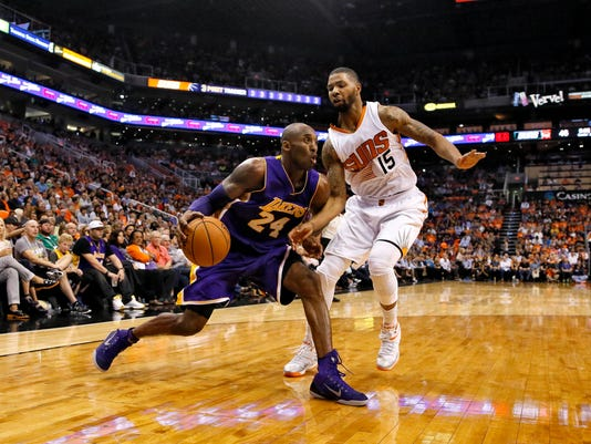 Los Angeles Lakers guard Kobe Bryant (24) drives against Phoenix Suns forward Marcus Morris (15) during the first half of an NBA basketball game, Wednesday, Oct. 29, 2014, in Phoenix. (AP Photo/Matt York)