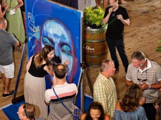 People at an Art of Everyone show paint a canvas guided