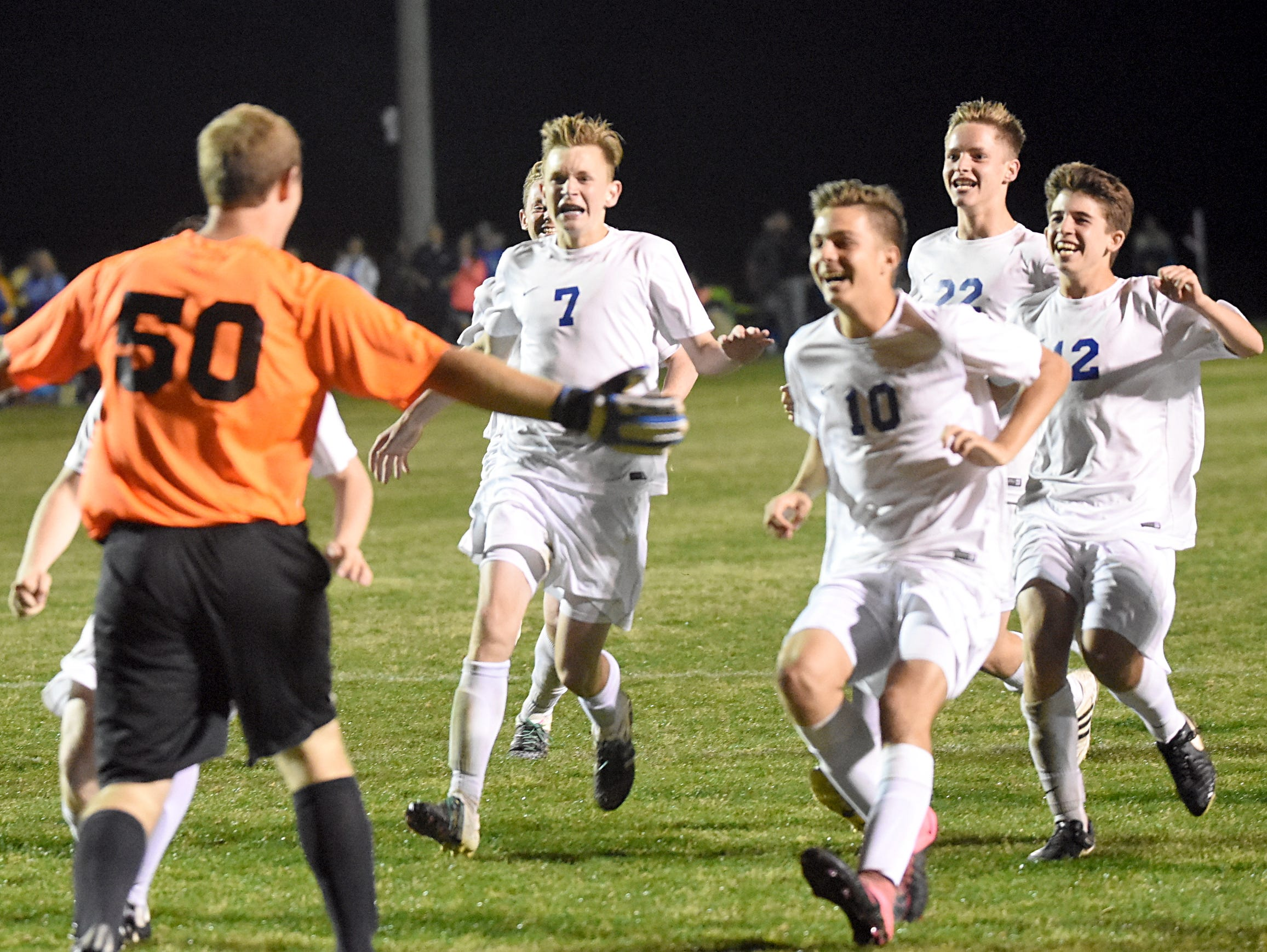 The White House High players run on to the field to celebrate with senior goalkeeper Logan Trimmer (50) after the Blue Devils defeated White House Heritage in a penalty-kick shootout in Friday evening's District 9 A-AA Tournament championship match.