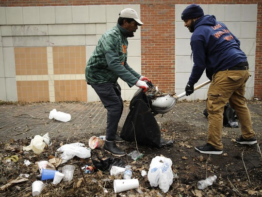 "In this Feb. 15, 2019, photo, Keith Q. Schenck, center, and Jordan P. Ferrarini take part in the Fresh Start initiative to clean up trash in the Germantown neighborhood of Philadelphia. Philadelphia has been trying for years to shed itself of the nickname ""Filthadelphia."" Now some neighborhoods struggling with litter have decided to take collection into their own hands. One has gone so far as to buy its own trash truck. (AP Photo/Matt Rourke)"