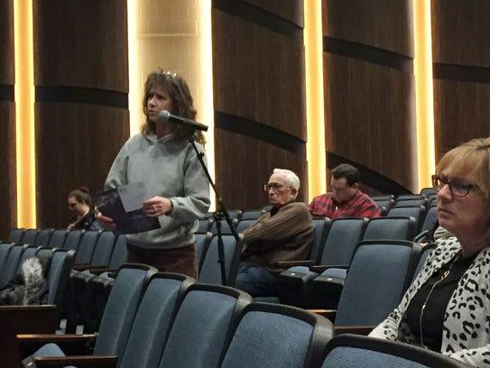 Colchester voter Carrie Neuschel, left, asks representatives