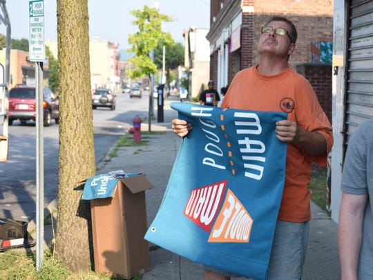 City of Poughkeepsie employee Mark Daniels prepares the first of 15 banners to be installed along Main Street in the City of Poughkeepsie.