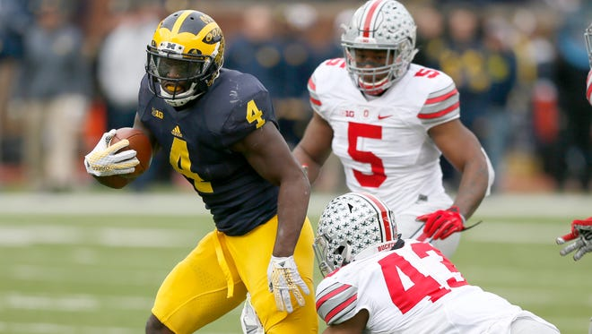 Michigan's De'Veon Smith break a tackle as he picks up a long first down to the 13 yard line setting up their touchdown in the last minute of the first half against Ohio State on Saturday, November 28, 2015, in Ann Arbor.