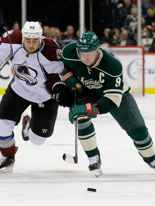 Colorado Avalanche center Ryan O'Reilly (90) and Minnesota Wild center Mikko Koivu (9), of Finland, chase the puck during the second period of Game 4 of an NHL hockey first-round playoff series in St. Paul, Minn., Thursday, April 24, 2014. (AP Photo/Ann Heisenfelt)