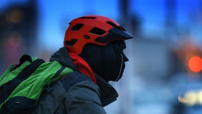 A bicyclist  in January bundles up against the extreme cold Downtown Indianapolis.