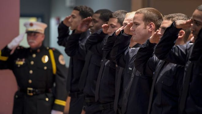 New firefighters salute during the pledge of allegiane during the Lafayette Fire Department's 98th Firefighter Academy Graduation at the Clifton Chenier Center in Lafayette, La., Friday, Feb. 27, 2015.