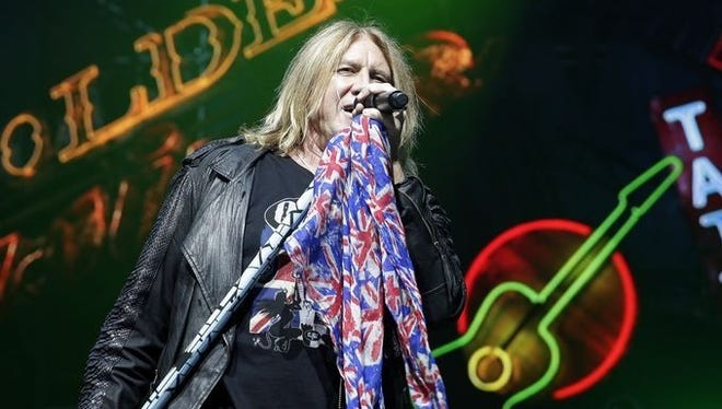 Def Leppard frontman Joe Elliott rocks a Union Jack scarf on his mic stand to open the band's sold-out concert Wednesday night at the Resch Center.