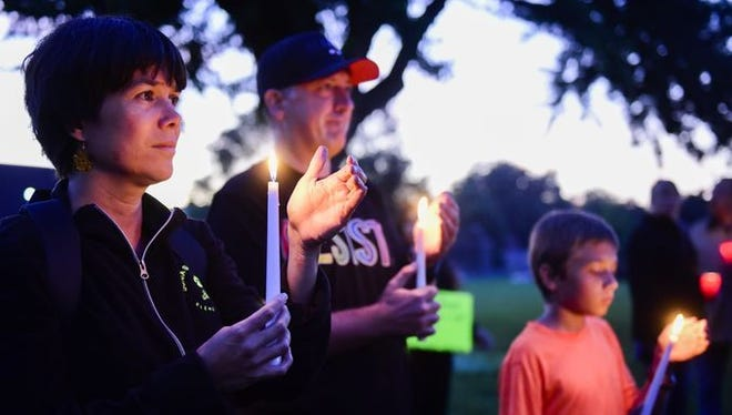 Pilar Cabrera, her husband Daniel, and son Falco (left to right) hold candles at a Meldrum Park vigil protesting President Trump's decision to end the DACA program.