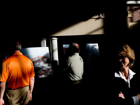 Members of the public examine renderings during a public