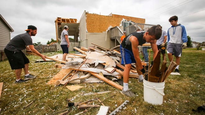 Members of the Bondurant-Farrar football team help clean up debris on the west end of Bondurant, Iowa, Friday, July 20, 2018, after a tornado slashed through the town Thursday afternoon.
