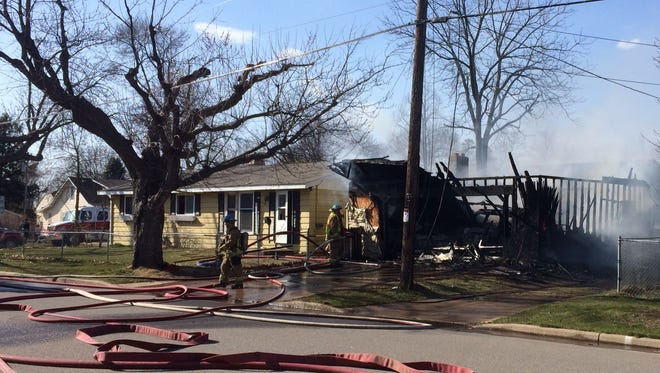 Wausau firefighters douse the garage destroyed by fire on the city's west side Sunday afternoon.