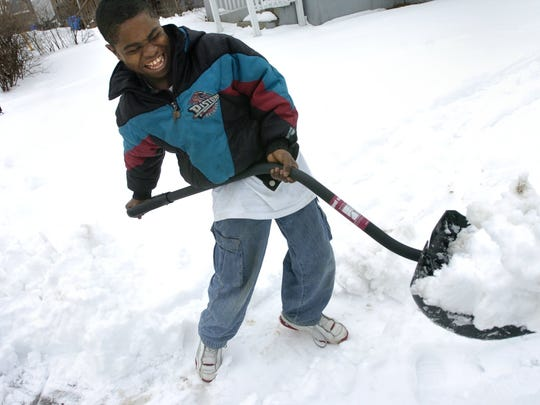 Ba Blamo, at the age of 7, shovels snow at the Lansing home where he lives in with his extended family. The family is from Liberia and have endured many hardships to eventually get to the United States.