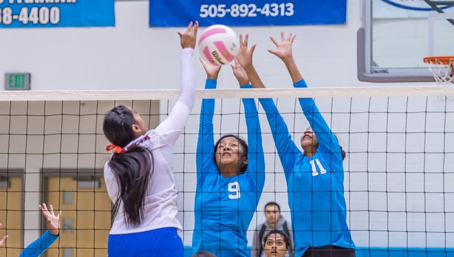 Navajo Prep's LeShauntai Adams (9) and Martinique Larvingo combine for a block against Estancia's Savanna Chavez during pool play at the 3A state volleyball tournament Thursday in Rio Rancho.
