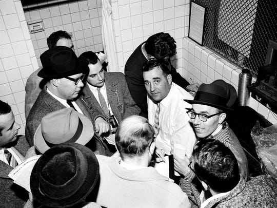 Sports writers crowd Detroit Lions head coach George Wilson, center, following his team's 59-14 victory over the Cleveland Browns in the NFL championship game in Detroit on Dec. 29, 1957.