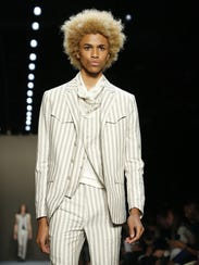 A model walks the runway in a three-piece striped suit