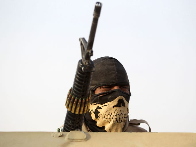 A masked member of the Iraqi forces looks on while