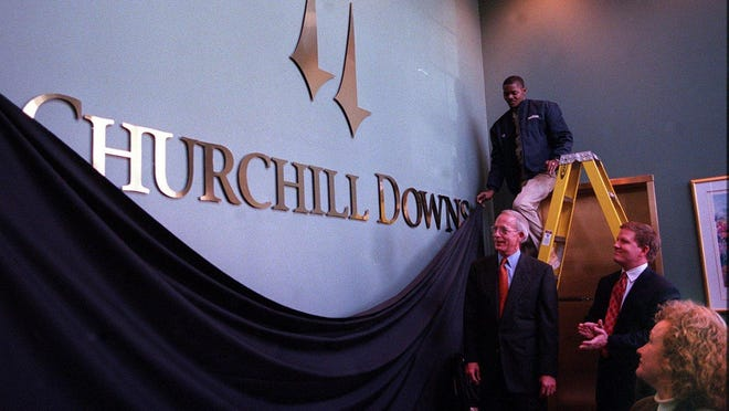 --Text: Special to the Courier-Journal. Photo BYBud Kraft. Feb9,2000. Churchill Downs unveiled it's new logo WEdnesday afternoon as Tom Meeker president of Churchill Downs Corp and Alex Waldrop (clapping) president of Churchill Downs racetrack watch. The lady watching is Claudia Lauber of Shandwick Publications. The man on the ladder is Curtis Taylor of Churchill Downs.--Caption: PHOTOS BY BUD KRAFT, SPECIAL TO THE COURIER-JOURNALTom Meeker, head of Churchill Downs Inc., and Alex Waldrop, president of Churchill Downs race track, attended the unveiling, as did Downs' employee Curtis Taylor, on ladder, and Claudia Lauber of Shandwick Publications.