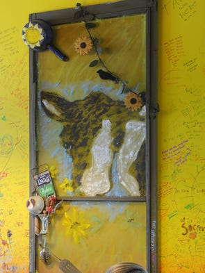 A cow peeks through a screen door as Ed Klepacki enjoys a cup of coffee at the Sparks Squeeze in.