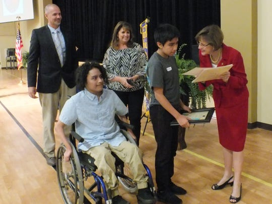 Rep. Gayle Harrell, right, gives Sydney Young Golden