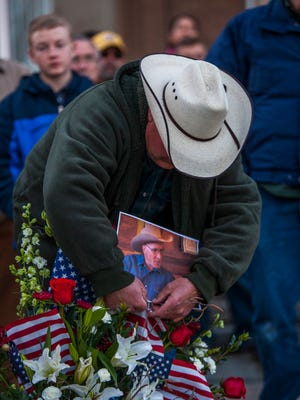 Phillip Gardener adjusts a photo of LaVoy Finicum on a bouquet arrangement during a memorial service for Finicum held in front of the Iron County Courthouse in Parowan, Wednesday, Jan. 27, 2016.