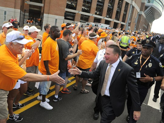Tennessee coach Butch Jones walks with Knoxville police