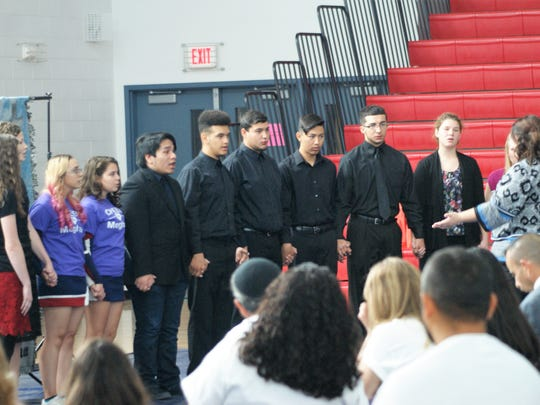 """The Deming High School Choir held hands as they sang """"Esto Les Digo"""" during the memorial service for Meghan Flores."""