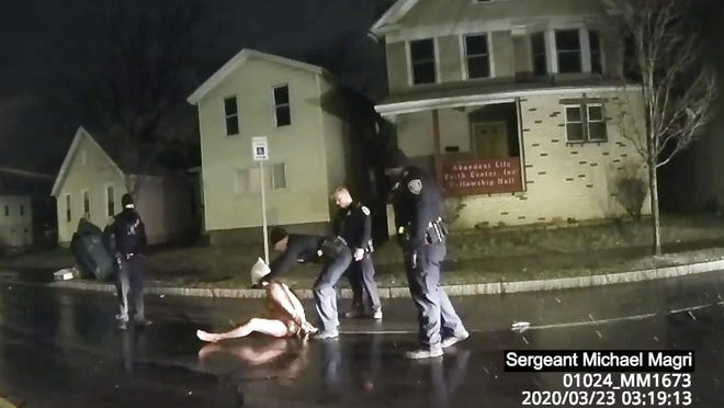 In this image taken from police body camera video provided by Roth and Roth LLP, a Rochester police officer puts a hood over the head of Daniel Prude, on March 23, 2020, in Rochester, N.Y. Video of Prude, a Black man who had run naked through the streets of the western New York city, died of asphyxiation after a group of police officers put a hood over his head, then pressed his face into the pavement for two minutes, according to video and records released Wednesday, Sept. 2, 2020, by his family. Prude died March 30 after he was taken off life support, seven days after the encounter with police in Rochester.