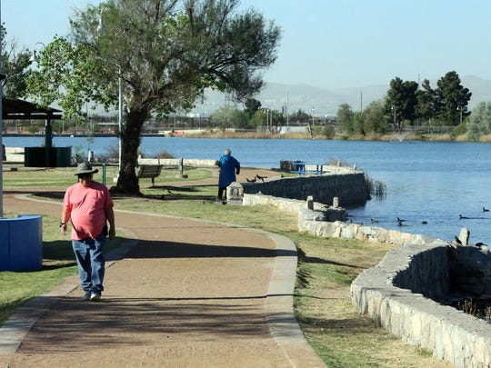 Daniel Acuña, left, of El Paso uses the walking trail around Ascarate Lake Thursday morning. Acuña said he tries getting out to the park 5-times per week.