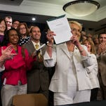 Lawmakers applaud after then-Gov. Jan Brewer signs the Medicaid expansion bill in 2013.
