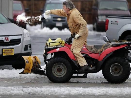 Glenn Reha, owner of Appleton Motorcars, salts the sidewalks near his business at the corner of Wisconsin Avenue and Mason Street in Appleton on Tuesday.