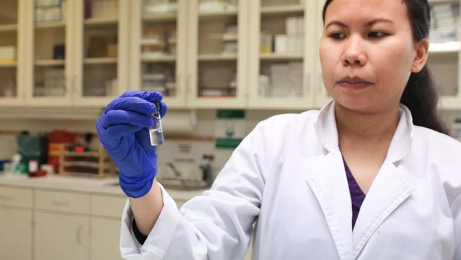 Lenoir County Health Department laboratory manager Charlin Silva holds a viral culture media that the department will freeze to keep a nose swab of a potential coronavirus alive to ship to a private state lab for testing.