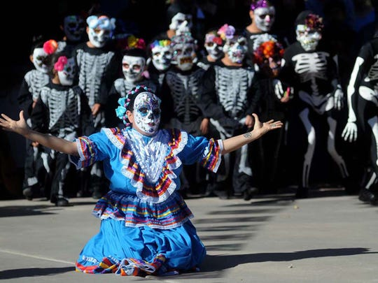 A member from the group Valle de Sol Grupo Folklorico of El Paso wears a traditional costume and skull mask as skeleton children run onto the Mesilla Plaza  during a recent  Dia de los Muertos celebration.