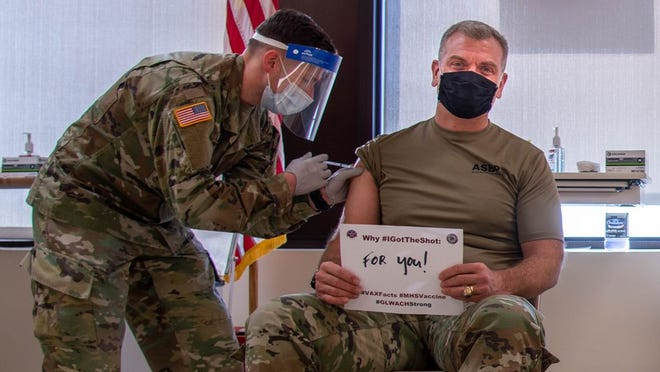 """Col. Aaron Pitney, General Leonard Wood Army Community Hospital commander, receives the COVID-19 vaccination. He said, """"when we ourselves choose to take the vaccine, we are actually protecting the Soldiers and service members to our left and right who we work and serve alongside."""""""