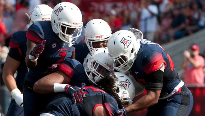 Oct 10, 2015: Arizona Wildcats defensive lineman Anthony Fotu (42) (bottom) is congratulated by teammates after an interception during the second quarter against the Oregon State Beavers at Arizona Stadium.