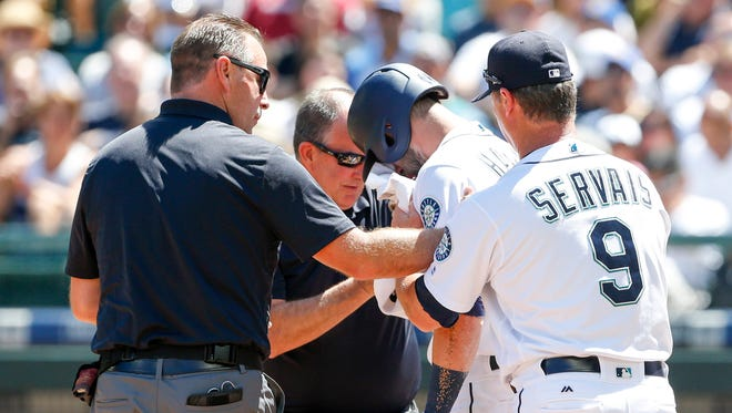 Mariners manager Scott Servais, right, and team staff tend to hitter Mitch Haniger after he was hit in the face by a pitch against the Mets during the second inning at Safeco Field in Seattle.