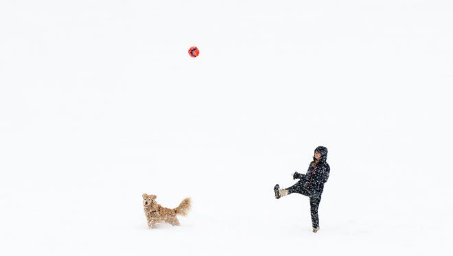 A woman plays with her dog at Riverfront Park during Friday's snowfall.