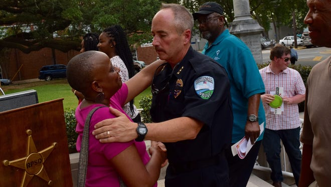 The Rev. Sherri L. Jackson (left) shakes hands with Alexandria Police Chief Loren P. Lampert at a prayer vigil held in July 2016. Lampert has announced his resignation from the department, effective July 15, 2017.